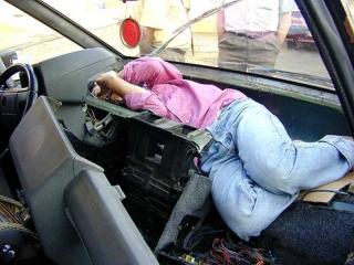 Persona escondida en el salpicadero de un coche
